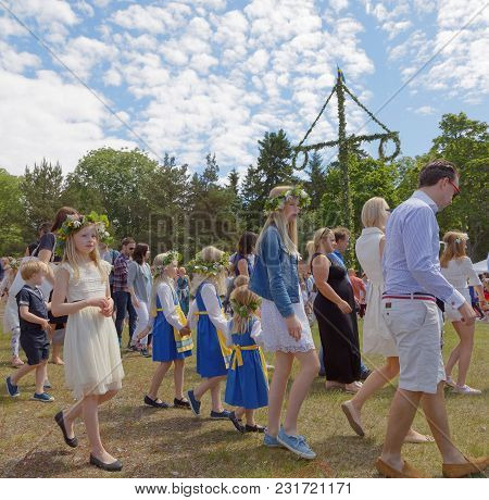 Vaddo, Sweden - June 23, 2017: Cchildren And Adults Dancing Around The Maypole Celebrating The Swedi