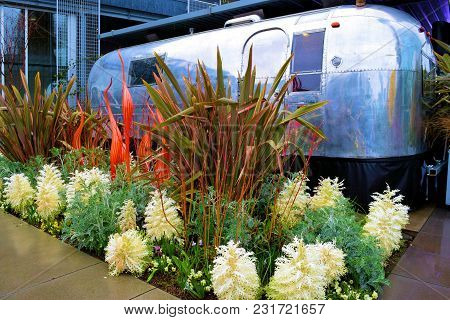 March 8, 2018 In Seattle, Wa:  Vintage Airstream Camper Surrounded By Plants And Flowers Taken At A