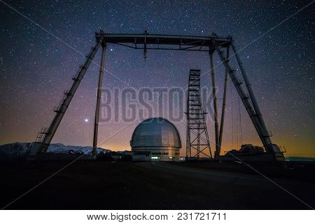 Night View. A Special Astrophysical Observatory And A Crane Against The Background Of The Starry Sky