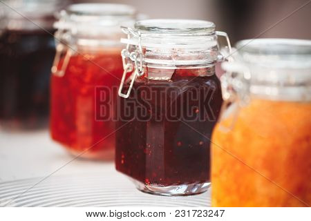 Glass Jars With Butter, Jam On The Wooden Shelf on Background Of A Dark Wall, Breakfast Concept, Ki