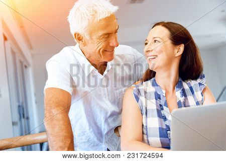 Happy modern mature couple working on laptop at home