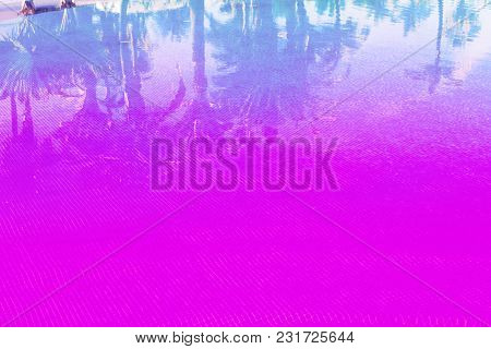 Summer Background With Blue Tiled Pool With Reflections Of Palm Trees, Toned In Pink