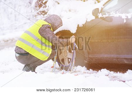 Man Installing Snow Chains On The Wheels Of Car.