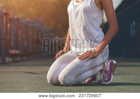 Close-up - Slim Brunette Young Woman Relaxing After Workout In Outdoors Gym At Sunny Summer Day.