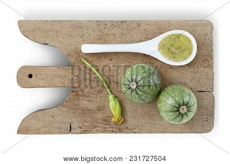 Zucchini On Wooden Cutting Board, Flower And Spoon Of Sauce Food Top View Isolated On White Backgrou