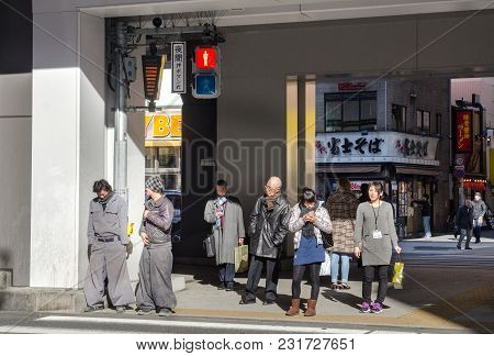 Tokyo, Japan - March 13, 2014: Japanese Pedestrians On Crosswalk Wait For Green Light