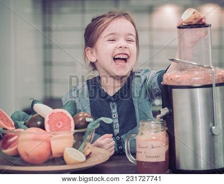 Little Cute Happy Girl Preparing Juice Fresh In The Kitchen, Concept Of Healthy Baby Food And Happy