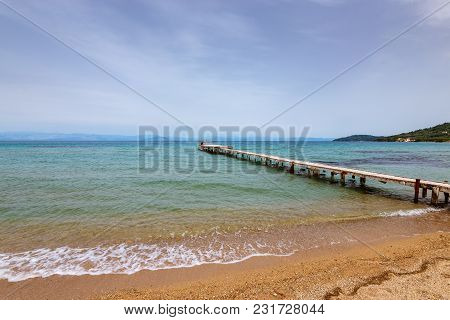 Old Wooden Pier And Sea In Cloudy Day. Eastern Side Of Corfu Island.