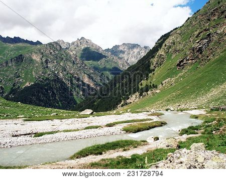 Small River Flows From The Rocky Mountains. Green Valley In A Summertime. Stones And Grasses. Uzunko