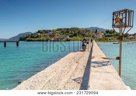 Corfu, Greece - May 13, 2016: Young Woman Riding A Scooter Through Causeway. Corfu Island, Greece