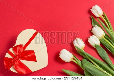 Colorful Spring White Tulip Flowers With A Decorative Heart Giftbox On Red Background As Greeting Ca