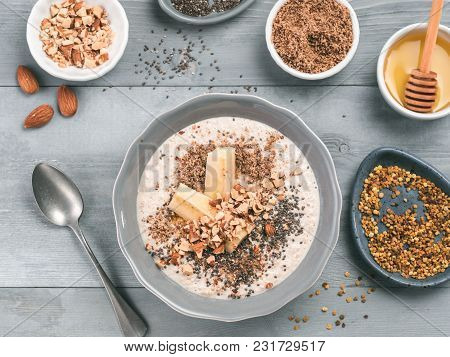 Overnight Oats In Bowl And Ingredients - Banana, Lsa, Chia Seeds, Almond, Honey And Pollen On Gray W