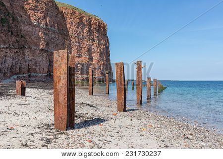 Beach Helgoland Island With Red Cliffs And Rusty Iron Pillars Of Old Putrefied Jetty