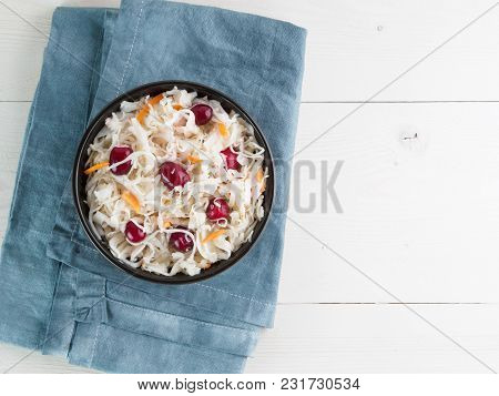 Traditional Russian Appetizer Sauerkraut With Cranberry And Carrot In Dark Craft Bowl On White Woode