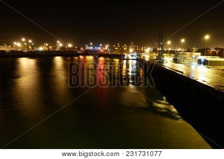The Seaport Of Zeebrugge. View At Night With Reflections Of City Lights On The Water.