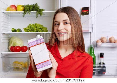 Photo Of Good Looking Young Female Dressed In Red Blouse, Holds Pack Of Milk, Stands Near Fridge Ful