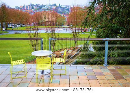March 8, 2018 In Seattle, Wa:  Public Courtyard With Patio Furniture Overlooking A Park With A Green