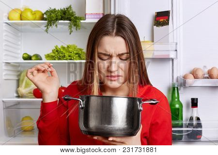 Pretty Woman Holds Saucepan, Feels Unpleasant Stink As There Is Spoiled Dish, Wears Red Blouse, Stan