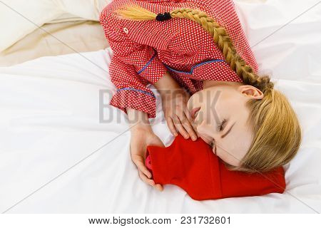 Woman Lying On Bed Sleeping With Warm Red Hot Water Bottle. Fever, Flu Treatment Objects Concept.