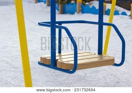 Children's Swing Is Empty On The Playground