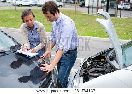Woman Driver And Man Reporting The Damage Of The Car After Accident