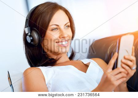 Young woman with headphones sitting at home