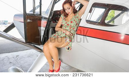 Young traveling girl in antique floral dress in a vintage plane from the 50s, travel and enjoy the adventures