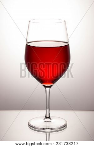 Glass Of Bright Red Wine On A High Stem On A Gray Background Is Very Beautiful And Healthy