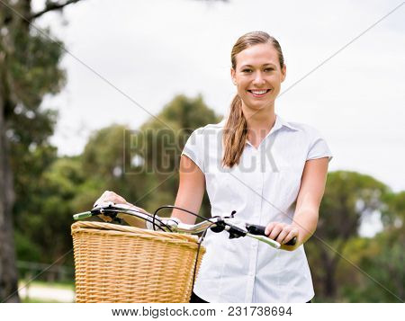 Beautiful young blonde woman with bike in park