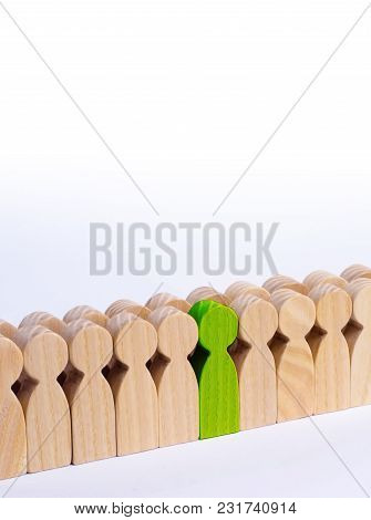 The Chosen Person Among Others. A Human Figure Of Green Color Stands In The Crowd. Wooden Figures Of
