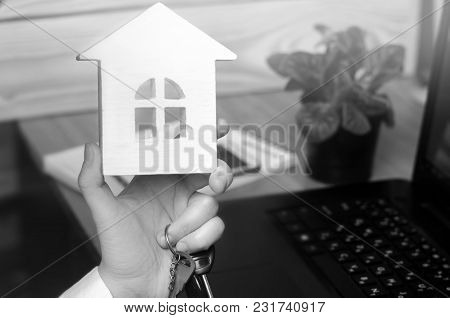 Keys And A Small House In Hands. Real Estate Agent. Concept Of Buying Apartments, Selling Apartments