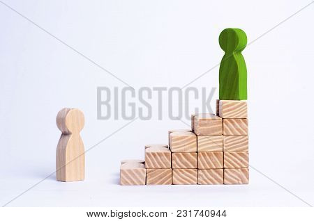 A Green Man Stands At The Top Of A Social Or Career Ladder. Concept Of Business Success. Stairs Of P