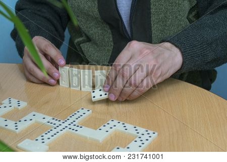 A Man In A Dark Wool Cardigan Is Playing At The Table At The Table, Holding The Dominoes In His Hand