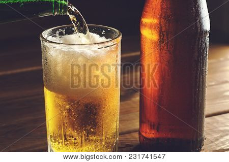 Pouring Foaming Beer Into Glass Mug With Drops Near Cold Beer Bootle, Close Up