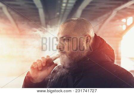 Vape Man. Young Guy Vaping Electronic Cigarette Or Vape Pen At Urban Background, Modern Lifestyle Co