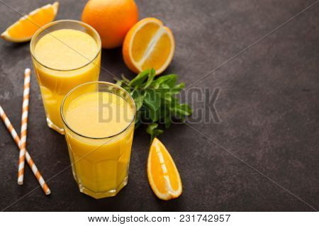 Two Glasses Of Freshly Squeezed Orange Juice And Mint On A Dark Brown Background. Top View With Copy