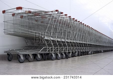 Row Of Empty Supermarket Carts, Inserted One Into Other, Leaving In Perspective