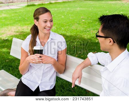 Portrait of smiling couple sitting in park and talking