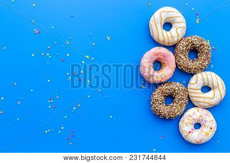 Donuts Decorated Icing And Sprinkles On Blue Background Top View Space For Text