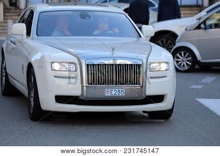 Monte-carlo, Monaco - March 17, 2018: Woman Driving An Expensive White Rolls-royce In Front Of The M