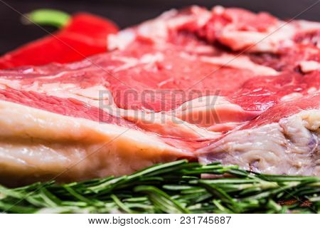 Close Up Raw Beef Steak On Wooden Cutting Board With Red Chili Pepper And Rosemary. Selective Focus