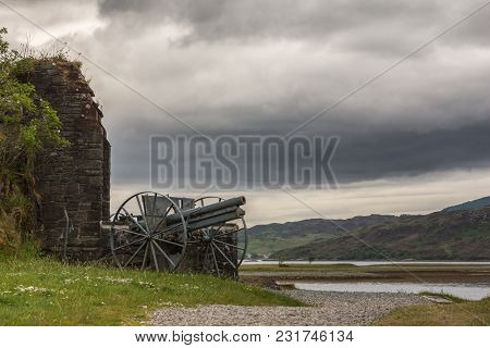 Dornie, Scotland - June 10, 2012: Historic Artillery Piece Outside Wall Of Eilean Donan Castle. Gree