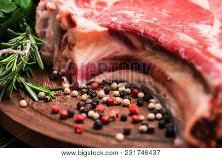 Close Up Raw Beef Steak On Wooden Cutting Board With Rosemary And Peppercorn. Selective Focus