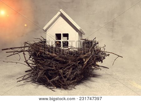 Buying, Selling A House, A White House In A Nest At Sunset. House Is An Investment.