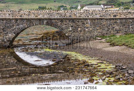 Dornie, Scotland - June 10, 2012: One Bow Of Footbridge To Eilean Donan Castle. Half Reflected On Wa
