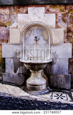Stone Decoration Water Source. Drinking Water Source With Ancient Roman Inscriptions