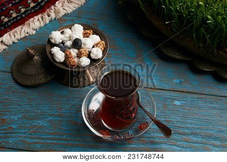 Turkish Tea In Traditional Glass And Copper Bowl With Sweet Snacks On Rustic Wooden Table Background