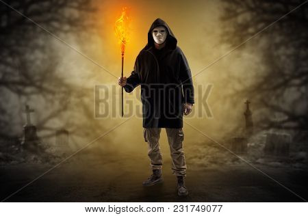 Man with burning flambeau coming from thicket and looking something