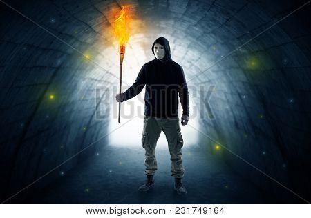 Ugly man with burning flambeau walking in a dark tunnel