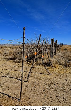 A Barbed Wire Gate Stretches Across A Dusty Desert Trail